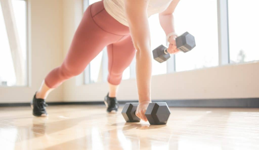 woman lifting weights in a plank position in a sunny gym t20 0x0Kp6